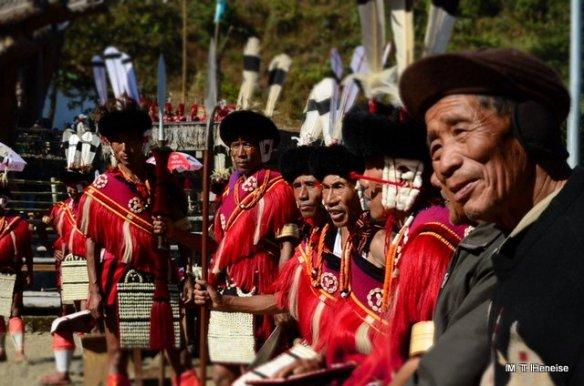 Sumi (Sema) Naga men in traditional ceremonial dress, resting near their morung at Naga Heritage Village, Kisama